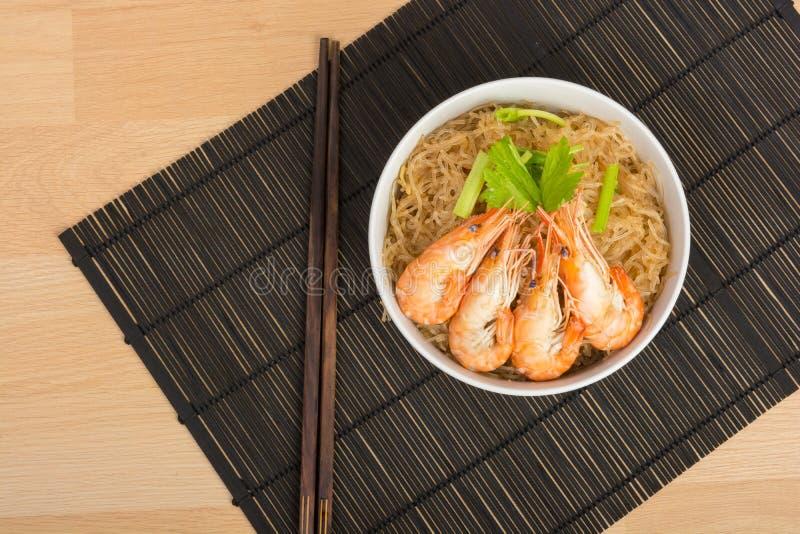 Fideos cocidos con el camarón en el plato de madera fotos de archivo libres de regalías