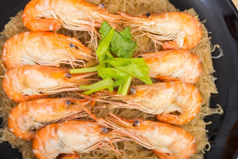 Fideos cocidos con el camarón en el plato de madera foto de archivo libre de regalías