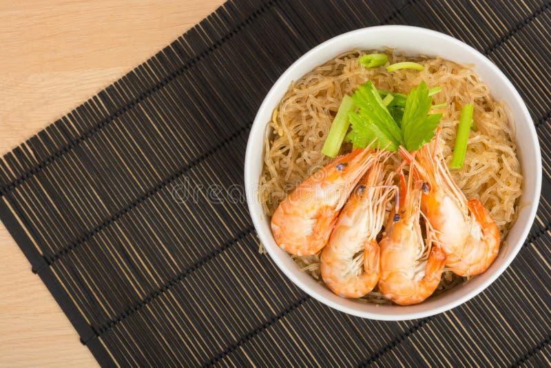 Fideos cocidos con el camarón en el plato de madera foto de archivo