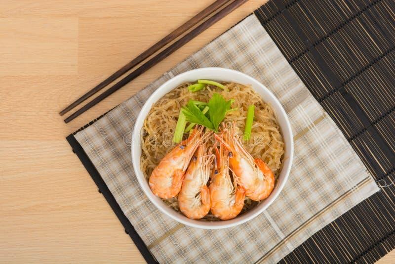 Fideos cocidos con el camarón en el plato de madera imágenes de archivo libres de regalías