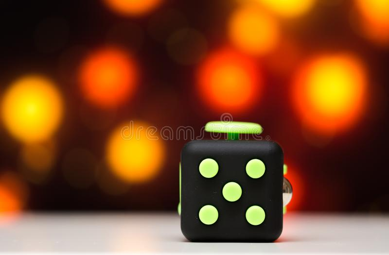 Fidget cube anti stress toy. Detail of finger play toy used for relax. Gadget placed on colorful bokeh background stock image