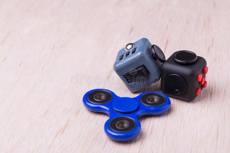 Fidget spinner and fidget cube, the latest stress relieving craze. On table top stock image
