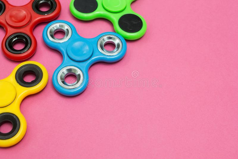 Fidget spinner stress relieving toy on the pink background. Space for text.  stock photos