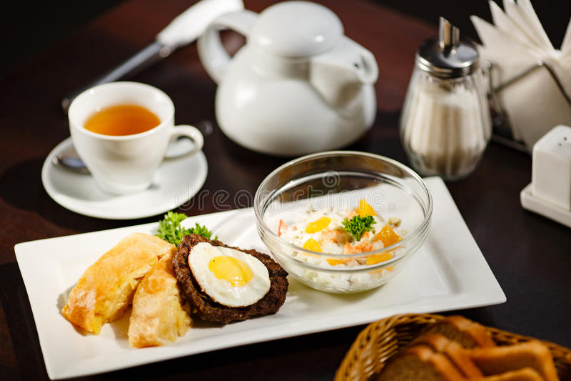 Fied jajko na mięsie z sałatką na talerzu zdjęcia stock