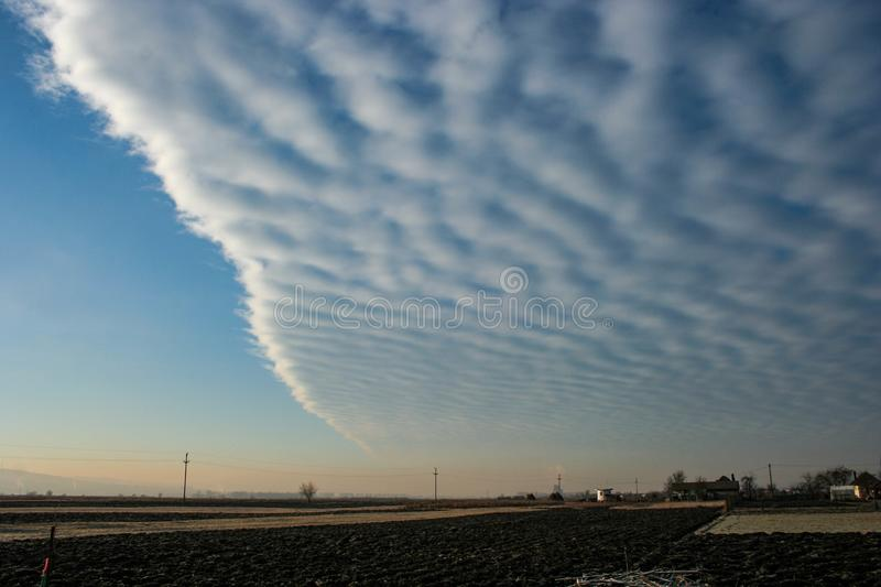 Field of altocumulus clouds with a sharp edge is invading the sky over Transylvania, Romania. royalty free stock image