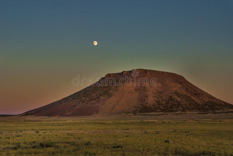 Field butte and moon sunset. Moon rises over a southern Idaho butte at sunset royalty free stock photo