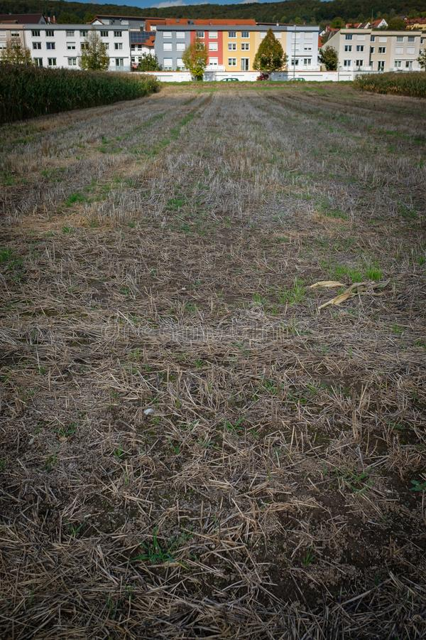 Field after crop in vertical format with terrace houses. In background royalty free stock photography