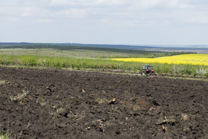 field den ploga traktoren royaltyfri bild