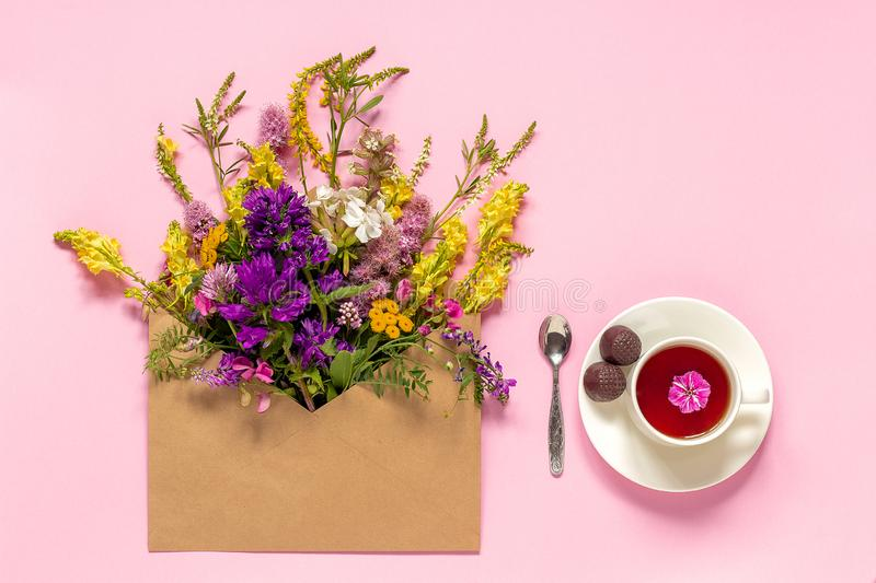 Field flowers in craft envelope and cup of herbs tea royalty free stock photography