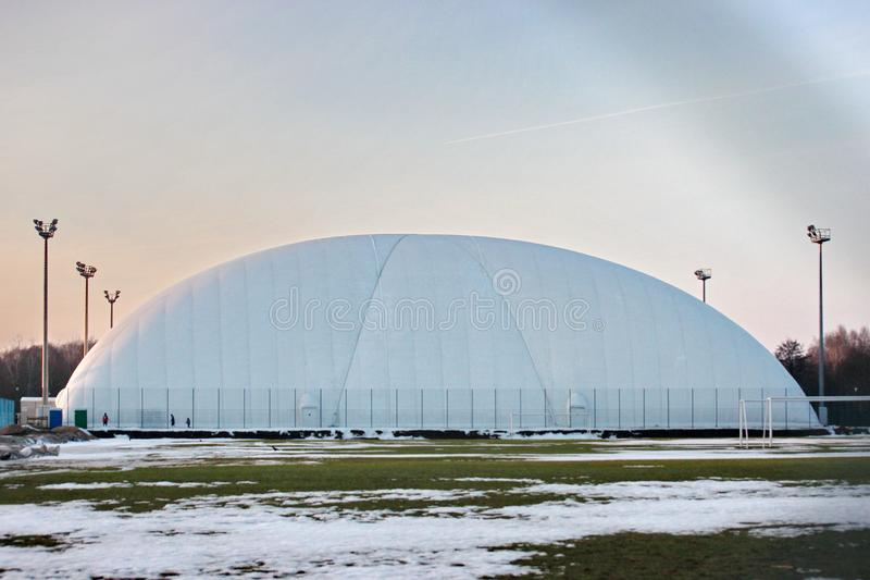Field for football or tennis in the winter time. stretched awning for protection and protection from weather conditions - snow. Field for football or tennis in royalty free stock photography