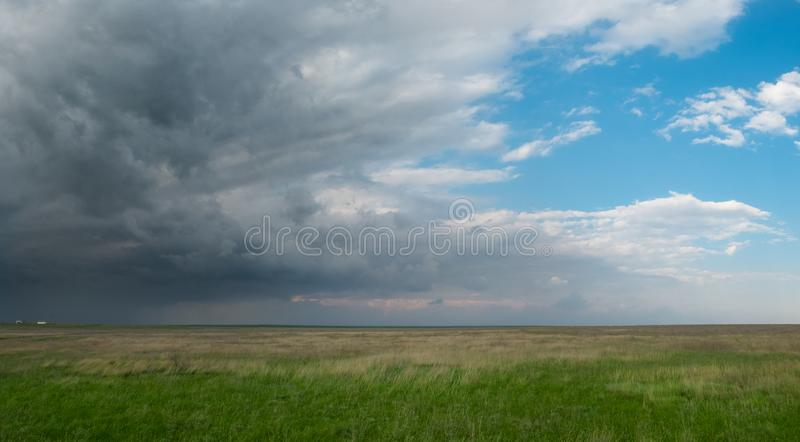 Field with green grass under a bright blue sky with large dark storm clouds stock image