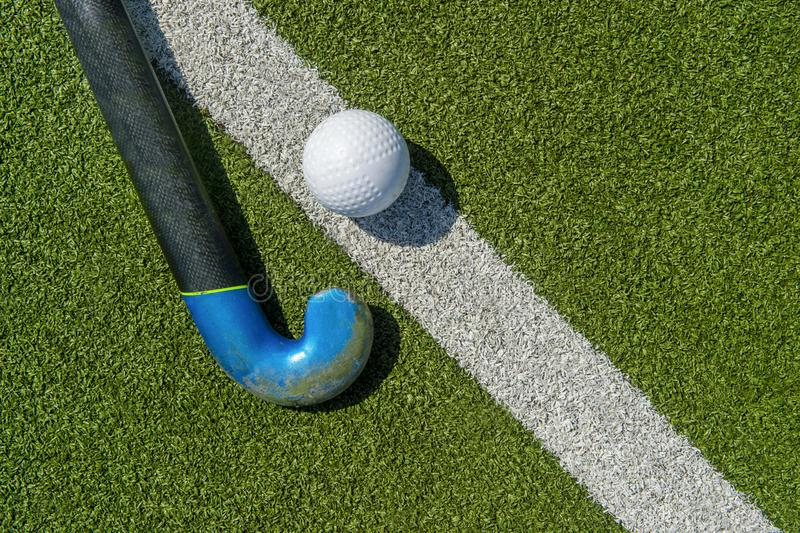 Field hockey stick and ball on the green field.  royalty free stock images