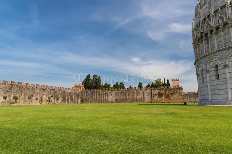 Field of Miracles Campo dei Miracoli next to the walls behind the Baptistery of St. John Battistero in Pisa, Tuscany, Italy royalty free stock photography