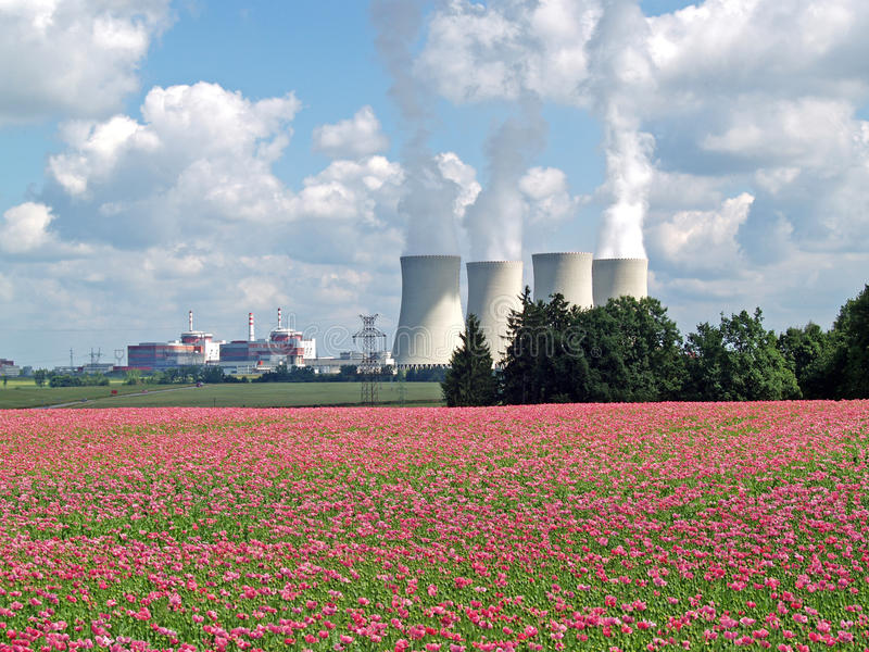 Field of poppy and nuclear power plant, Temelin. Cooling towers in the vicinity of fields, South Bohemia, Europe royalty free stock images