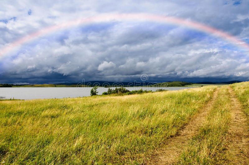 Download Field Road And Rainbow Over Lake Royalty Free Stock Photography - Image: 13170917