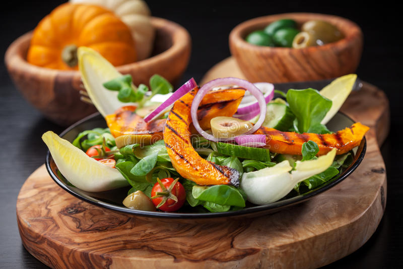 Field salad with grilled pumpkin. Delicious field salad with grilled pumpkin stripes for Thanksgiving stock image