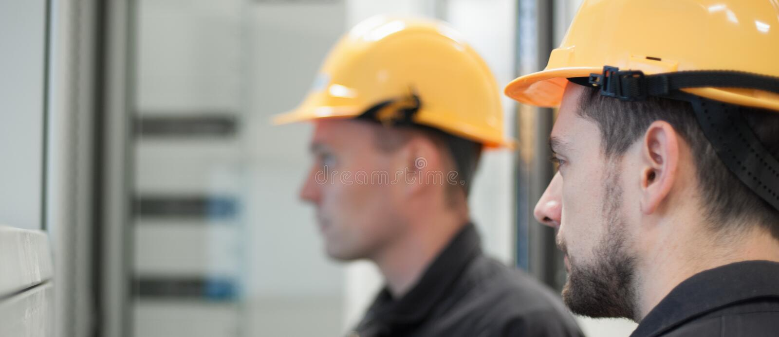Field service crew testing electronics or inspecting electrical. Installation system. Bay control unit. Medium voltage switchgear stock images