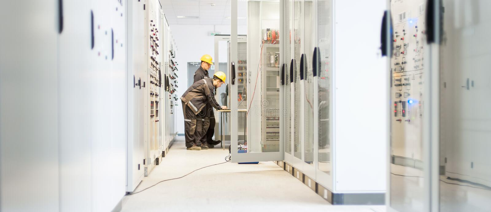Field service crew testing electronics or inspecting electrical. Installation system. Bay control unit. Medium voltage switchgear stock photos
