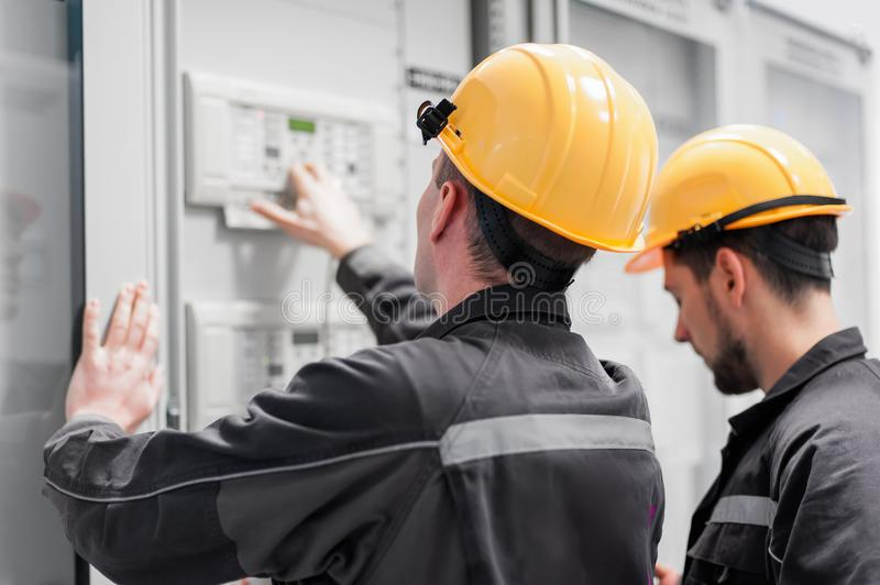 Field service crew testing electronics or inspecting electrical. Installation system. Bay control unit. Medium voltage switchgear royalty free stock photography