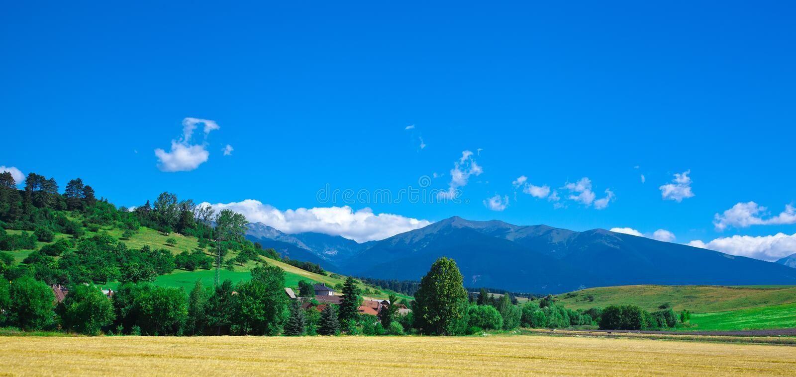 Field and the small village against Tatra mountains royalty free stock photography
