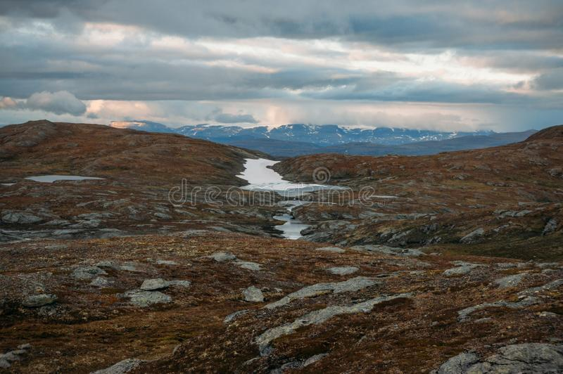 Field with small water ponds and mountains on background during stormy weather, Norway, Hardangervidda. National Park stock photo
