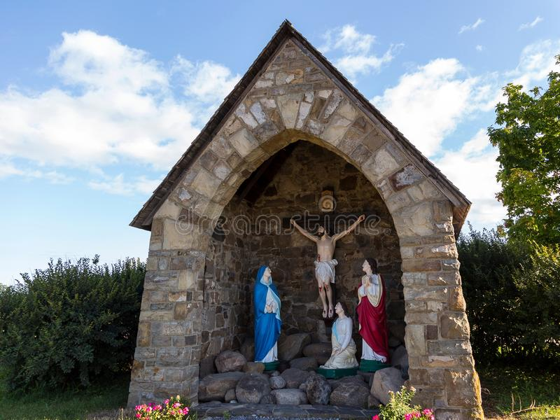Field stone grotto calvary with statues of holy family stock image