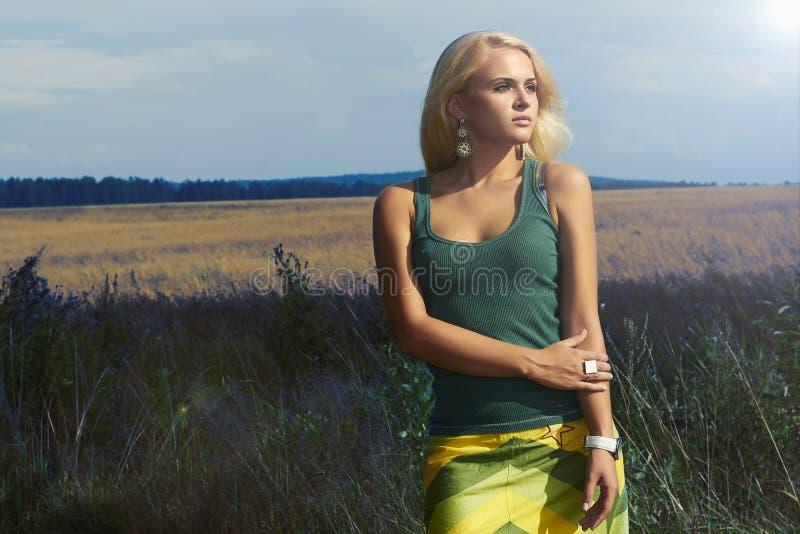field.Summer.Flowers的美丽的白肤金发的妇女 库存图片