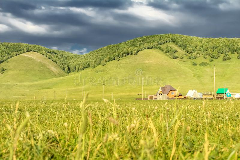 Field of summer green grass, green hills, houses in the distance and sky with thunder clouds. Field of summer green grass, green hills, houses in the distance royalty free stock images