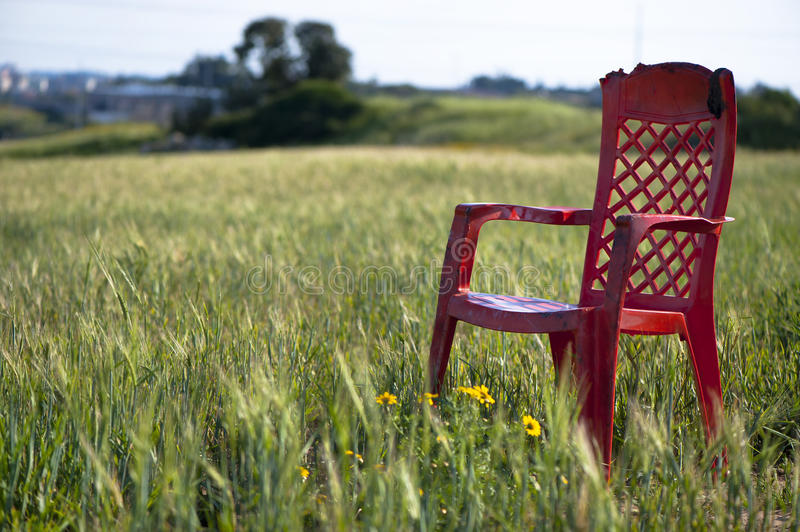 Field Tranquility. Red plastic chair in the middle of oats field on a spring sunny day. Peace and tranquility stock image