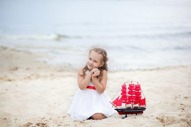 field treen Bekymmerslös lek för lycklig barndom på den öppna sanden Begreppet av vilar flickan på havet med ett skepp St?ende av royaltyfria foton