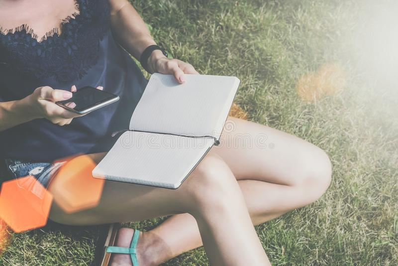 field treen Närbilden av smartphonen och notepaden i hand av sammanträde för den unga kvinnan parkerar in på gräsmatta och läsebo arkivfoto