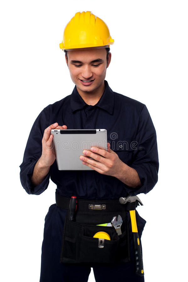 Field worker accessing touch pad. Young mechanical engineer accessing touch pad device stock photography