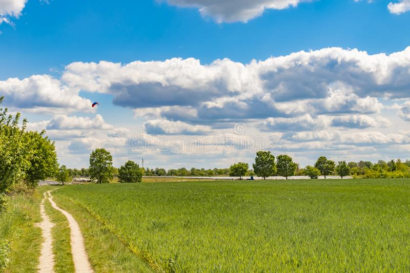 Fields at the city boundary between Berlin and Brandenburg, Germany. Over the landscape, white clouds can be seen in a bright blue. Sky. Between fields and royalty free stock photos