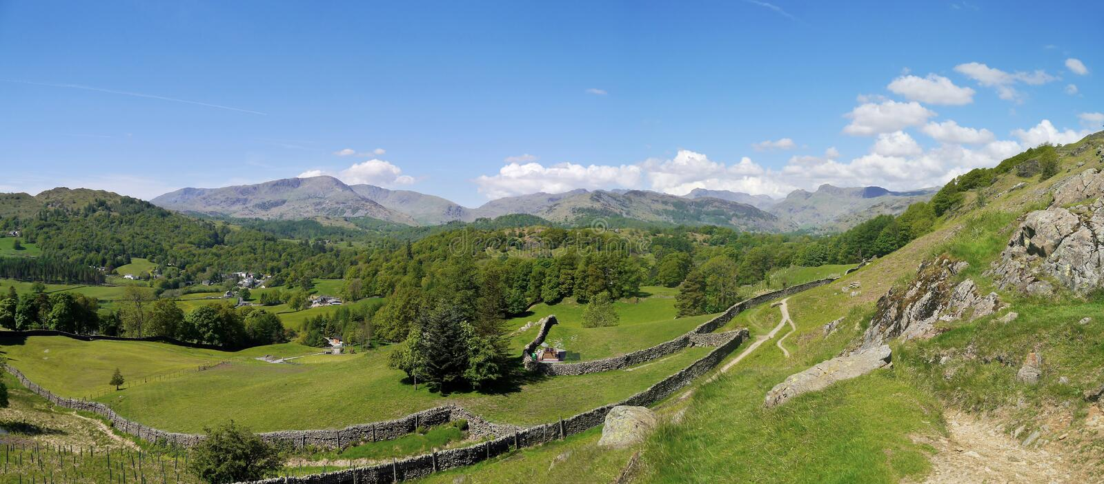 Fields with distant hills behind, panoramic. Panoramic view of Lake District hills stock photos
