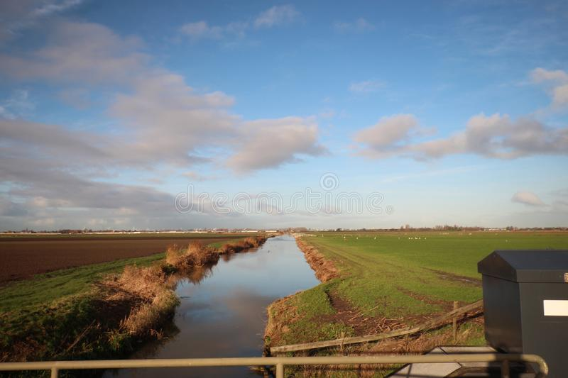 Fields and meadows along Hollandsche IJssel river with blue sky and white clouds. The polder behind the is named zuidplaspolder an royalty free stock images