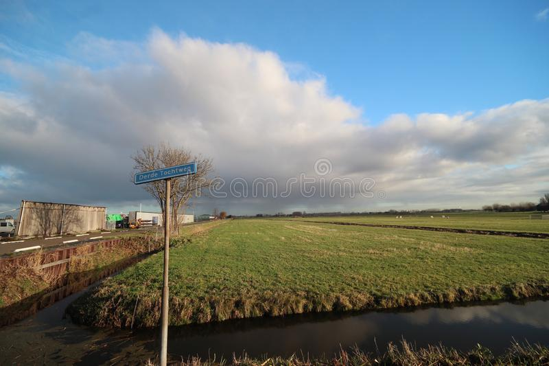 Fields and meadows along Hollandsche IJssel river with blue sky and white clouds. The polder behind the is named zuidplaspolder an stock photography