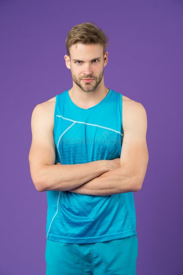 Fier d'être fort L'équipement sportif d'homme semble sérieux et strict avec les bras pliés, fond violet Corps musculaire de type images libres de droits