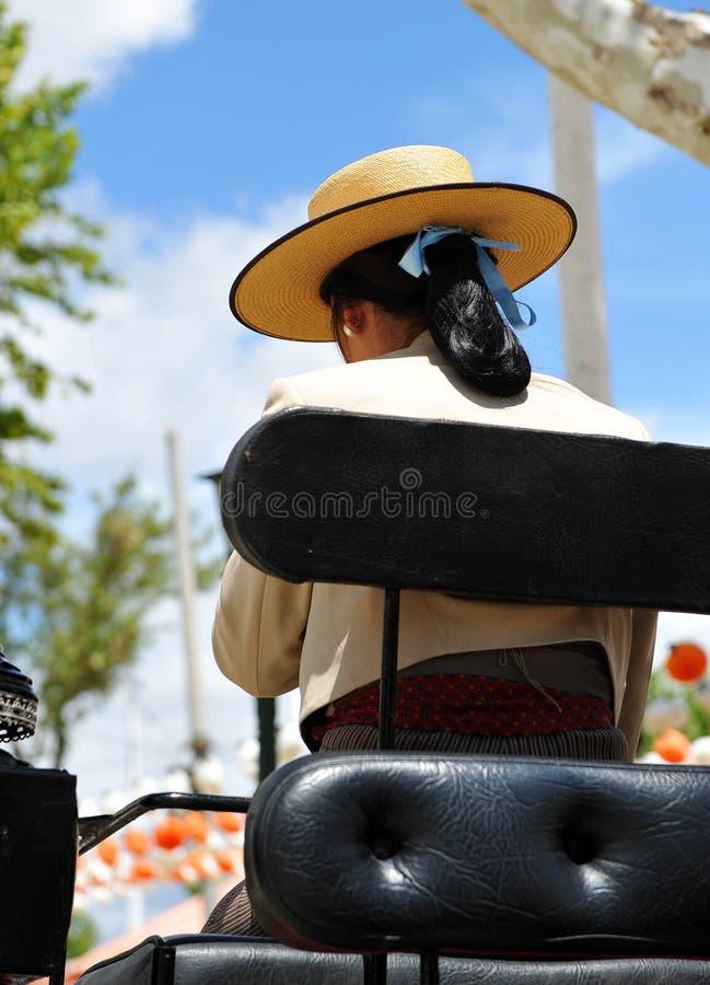 Fiera di Siviglia, donna con il cappello su un trasporto del cavallo fotografia stock