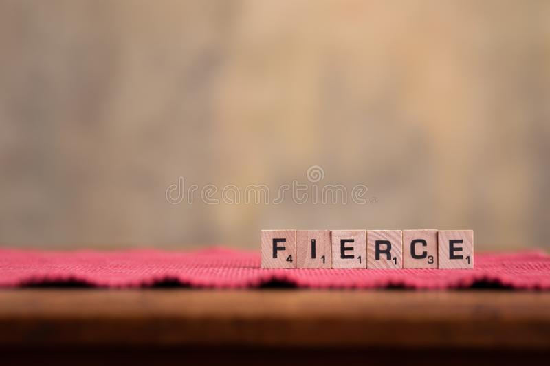 Fierce Words. Scrabble letters spelling fierce on fabric and wood background royalty free stock photos
