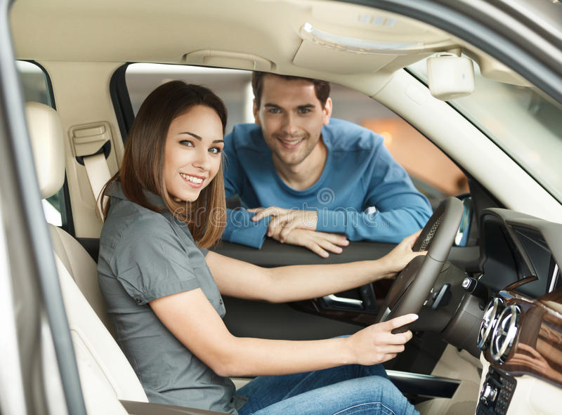 Fiero della loro nuova automobile. Le belle giovani coppie stanno esaminando una n fotografia stock libera da diritti