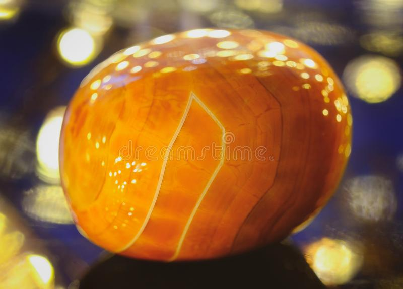 Fiery agate. Polished fire agate on a beautiful glowing background stock images