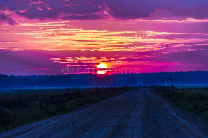 Fiery clouds in the rays of the rising sun. And the road leading into the forest stock photography