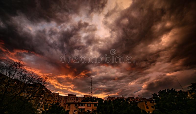 Fiery darkness before the storm. Epic fiery orange-black clouds during sunset over the neighbourhood just before the storm unleashed royalty free stock photo
