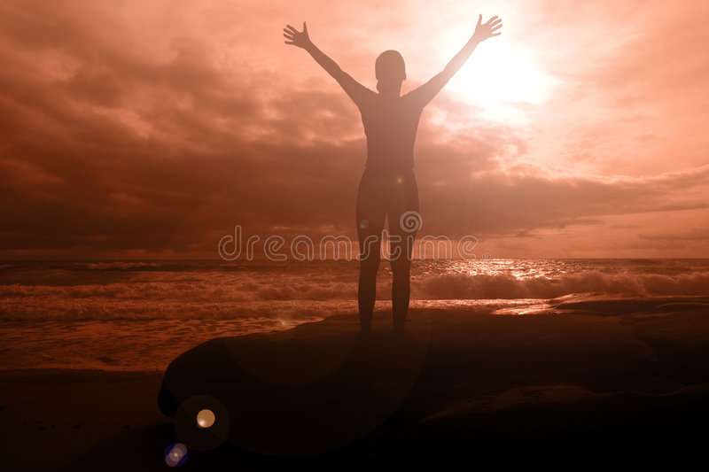Fiery glory. Woman with arms raised on a fiery sunset seascape with dramatic clouds royalty free stock photography