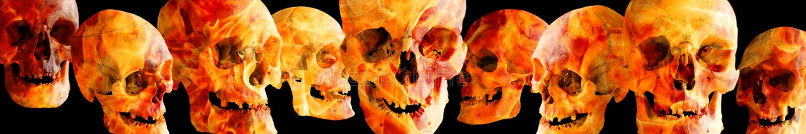 Fiery human skulls at different angles on a black background. The header or footer of the image. Isolated on black stock photography