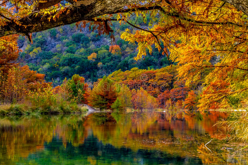 Fiery Orange Reflections on the Frio River at Garner State Park, Texas. Beautiful Fiery Orange Fall Foliage Reflecting off the Crystal Clear Frio River in Texas royalty free stock photography