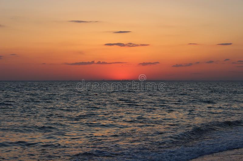 Fiery red sunset over the sea. The silhouette of the city stock photography