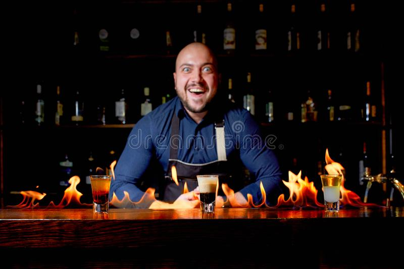 Fiery show at the bar. The bartender makes hot alcoholic cocktail and ignites bar. Bartender prepares a fiery cocktail. Fire on bar royalty free stock photos
