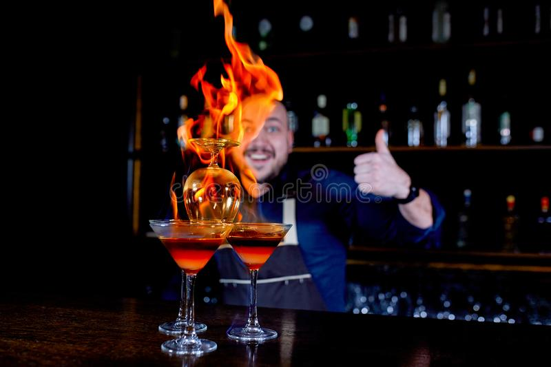 Fiery show at the bar. The bartender makes hot alcoholic cocktail and ignites bar. Bartender prepares a fiery cocktail. Fire on bar royalty free stock photography