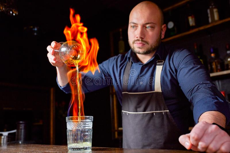Fiery show at the bar. The bartender makes hot alcoholic cocktail and ignites bar. Bartender prepares a fiery cocktail. Fire on bar royalty free stock photo